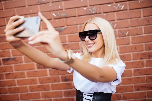 Piękna Blondynka Kobieta Dziewczyna Robi Selfie Na Smartfonie, Stojąc Przed Murem Z Czerwonej Cegły. Darmowe Zdjęcia