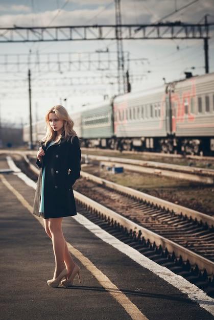 Piękna blondynki dziewczyna czeka pociąg przy stacją. romantyczny, delikatny wygląd Premium Zdjęcia