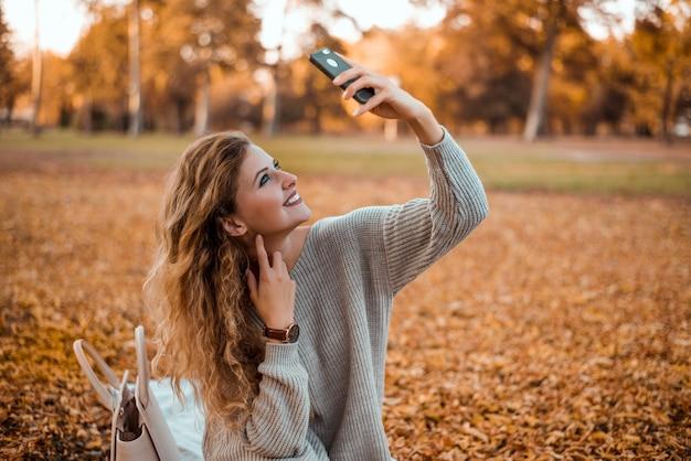 Piękna Blondynki Dziewczyna Jest Ubranym Nowożytnego Jesień Strój Siedzi W Parku W Jesieni Bierze Selfie Na Smartphone. Premium Zdjęcia