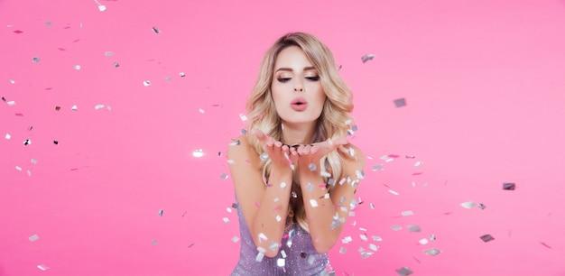 Piękna blondynki kobieta świętuje nowego roku lub wszystkiego najlepszego z okazji urodzin przyjęcia rzuca confetti na menchiach Premium Zdjęcia