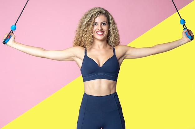 Piękna blondynki kobieta z kędzierzawymi włosami robi ćwiczeniom i rozciąga się z gumowymi opaskami Premium Zdjęcia