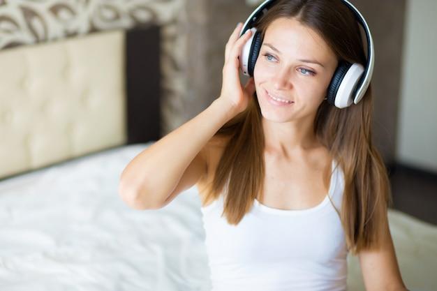 Piękna brunetka dziewczyna ze słuchawkami w sypialni Premium Zdjęcia
