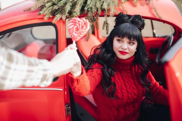 Piękna Brunetka Kobieta W Sweter Z Dzianiny, Trzymając Lizaka I Wysiadając Z Rocznika Czerwonego Samochodu Darmowe Zdjęcia