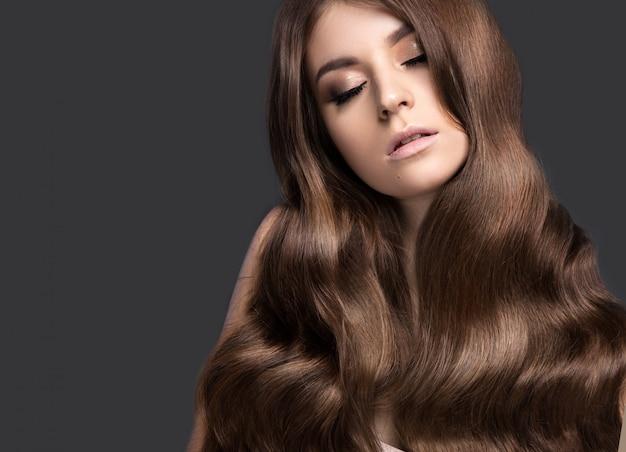 Piękna Brunetka O Idealnie Kręconych Włosach I Klasycznym Makijażu Premium Zdjęcia