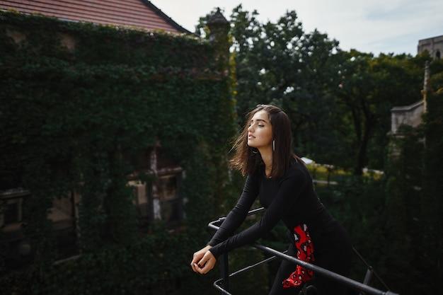 Piękna brunetka pozowanie na czarne schody Darmowe Zdjęcia