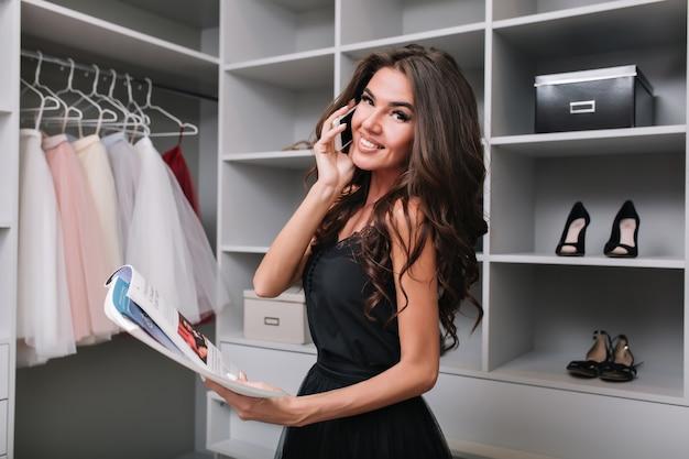 Piękna Brunetka Rozmawia Przez Telefon W Garderobie I Czytając Magazyn. Zajęte życie Stylowej Kobiety. Ma Długie, Piękne Włosy, Ubrana W Czarną ładną Sukienkę. Darmowe Zdjęcia