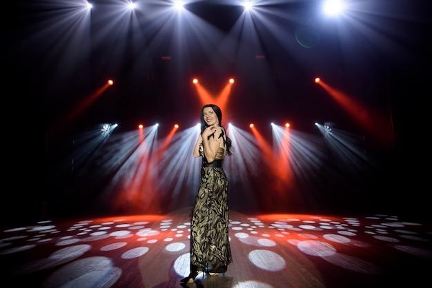 Piękna Brunetka W Długiej Sukni Na Scenie Z Jasnym światłem. Ciemnoczerwone Tło, Dym, Reflektory Koncertowe. Premium Zdjęcia