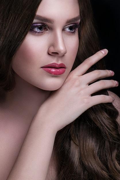 Piękna brunetka z długimi włosami i makijażem pozuje Premium Zdjęcia