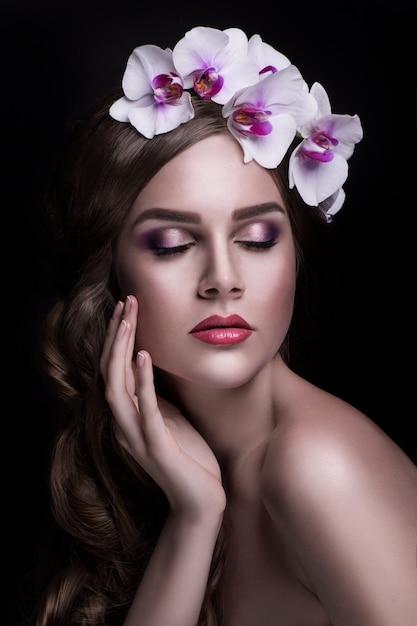 Piękna brunetka z długimi włosami i wieniec z kwiatów Premium Zdjęcia