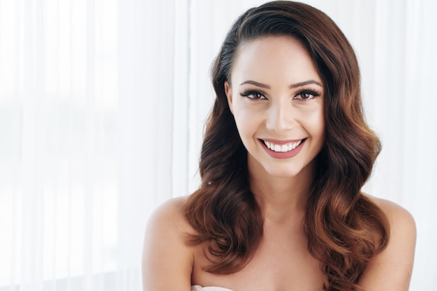 Piękna brunetka z makijażem, falowane włosy i nagie ramiona, pozowanie i uśmiechając się Darmowe Zdjęcia