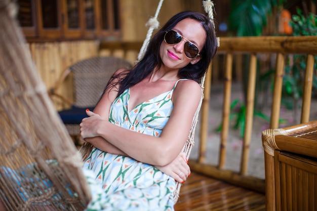 Piękna brunetki kobieta relaksuje w hamaku przy egzotycznym hotelem na filipiny Premium Zdjęcia