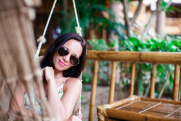 Piękna brunetki kobieta relaksuje w hamaku przy egzotycznym luksusowym hotelem Premium Zdjęcia