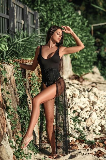 Piękna Brunetki Kobieta W Czarnym Swimsuit I Przylądku Pozuje Na Plaży Premium Zdjęcia