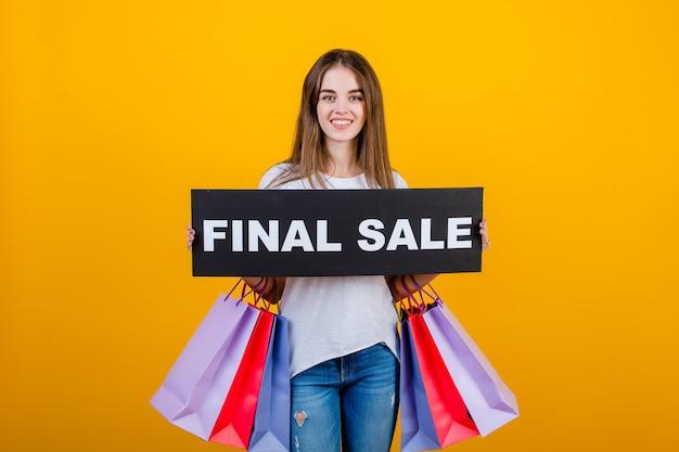 Piękna brunetki kobieta z kolorowymi torba na zakupy i copyspace teksta definitywnej sprzedaży znaka sztandarem odizolowywającym nad kolorem żółtym Premium Zdjęcia