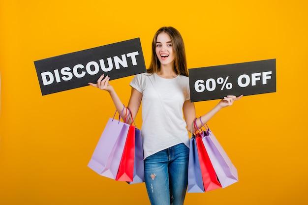 Piękna brunetki kobieta z kolorowymi torba na zakupy i copyspace teksta rabatem 60% szyldowy sztandar odizolowywający nad kolorem żółtym Premium Zdjęcia