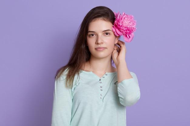 Piękna Brunetki Młoda Kobieta Jest Ubranym Przypadkową Odzież Trzyma Różowego Peonia Kwiatu Za Jej Ucho Darmowe Zdjęcia