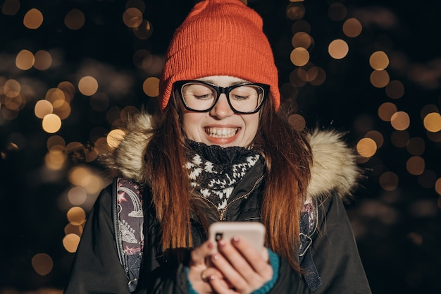 Piękna Caucasian Kobieta Używa Mądrze Telefon Ręki Chwyta Plenerowego W Miasto Nocy, Ono Uśmiecha Się, Twarz Iluminujący Screenlight Premium Zdjęcia