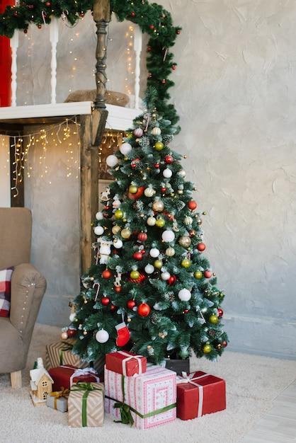 Piękna choinka z czerwonymi, białymi i złotymi kulkami i prezentami pod nią w salonie domu lub mieszkania Premium Zdjęcia