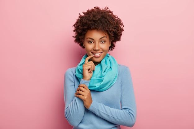 Piękna Ciemnowłosa Kobieta Ożywia Rozmowę, Rozmawia Z Przyjaciółką O Czymś Przyjemnym, Nosi Niebieski Sweter I Szalik, Dotyka Warg Palcem Wskazującym Darmowe Zdjęcia