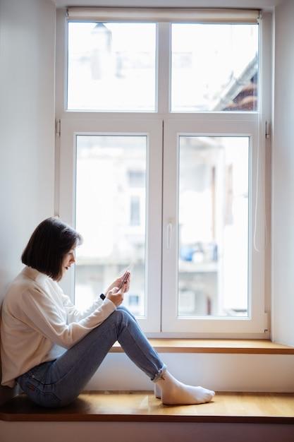 Piękna Dama W Pokoju Siedzi W Pobliżu Okna W Ubranie Z Telefonem Darmowe Zdjęcia