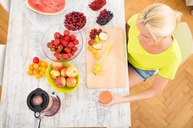 Piękna Dojrzała Kobieta Popijająca Smoothie Lub Sok Z Owocami W Kuchni. Premium Zdjęcia