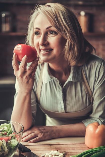 Piękna Dojrzała Kobieta W Fartuchu Wącha Pomidoru. Premium Zdjęcia