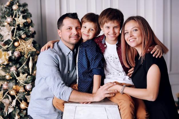 Piękna duża rodzina spędza czas w domu w pobliżu choinki Premium Zdjęcia