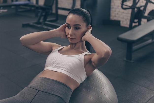Piękna dysponowana kobieta robi abs chrupnięciom na sprawnościowej piłce, pracująca na gym Premium Zdjęcia