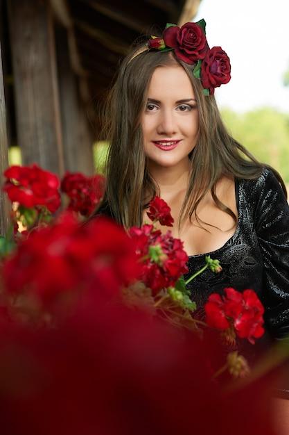 Piękna Dziewczyna, Brunetka W Czerwonej Koronie, Otoczona Czerwonymi Kwiatami, Portret. Darmowe Zdjęcia