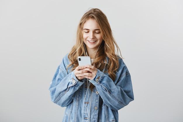 Piękna Dziewczyna College'u Sms-y, Wiadomości I Słuchanie Muzyki W Słuchawkach Darmowe Zdjęcia