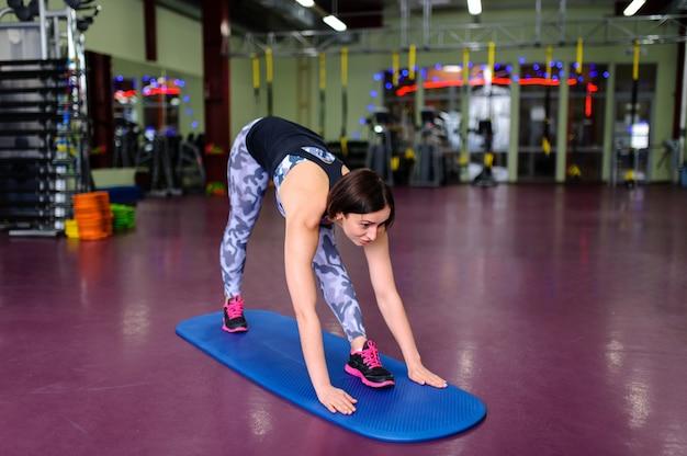 Piękna dziewczyna karate na macie na siłowni. Premium Zdjęcia