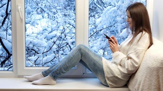 Piękna Dziewczyna Na Siedzącym Parapecie, Za Pomocą Smartfona. Zima Na Zewnątrz. Premium Zdjęcia