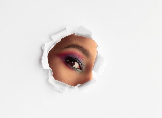 Piękna Dziewczyna Patrzeje Przez Round Poszarpanej Dziury W Białego Papieru Tle Z Makeup. Premium Zdjęcia
