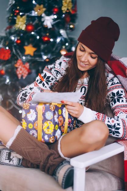 Piękna dziewczyna pisze list do świętego mikołaja, siedząc przy choince w domu. Premium Zdjęcia