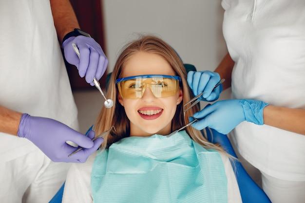 Piękna dziewczyna siedzi w gabinecie dentystycznym Darmowe Zdjęcia