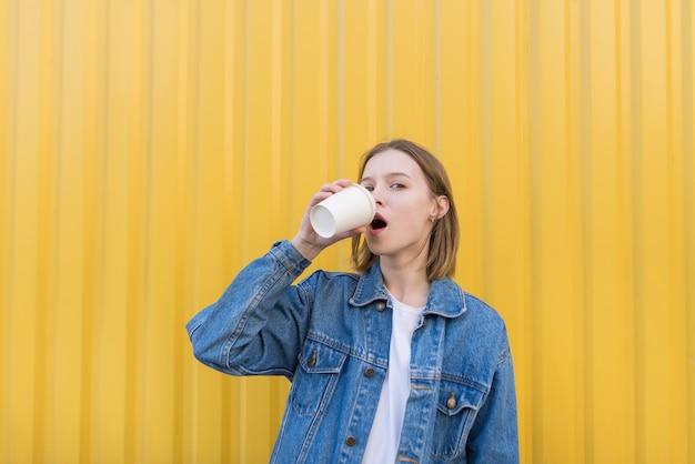 Piękna Dziewczyna Stoi Na Tle żółtej ściany I Pije Kawę Z Filiżanki. Premium Zdjęcia