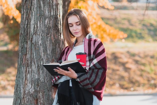 Piękna dziewczyna trzyma książkę i filiżankę Darmowe Zdjęcia