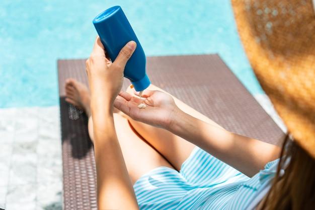 Piękna Dziewczyna Ubrana W Strój Kąpielowy, Stosując Krem Do Opalania I Relaks Przy Basenie Premium Zdjęcia