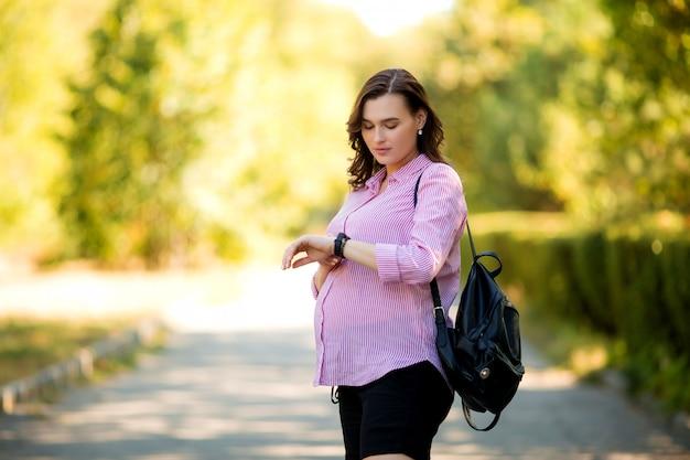Piękna dziewczyna w ciąży na letni spacer Premium Zdjęcia