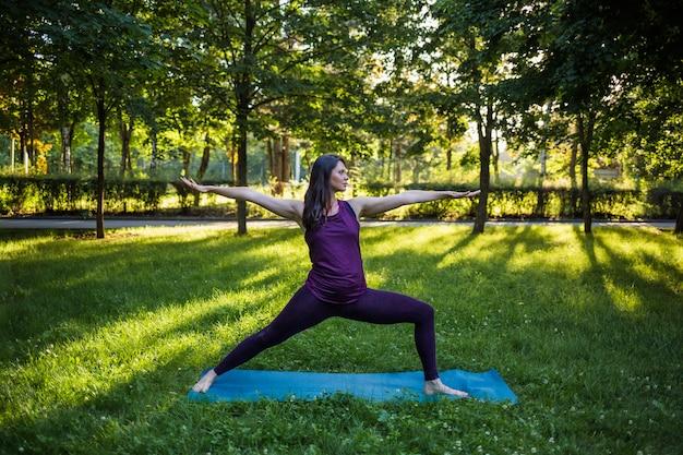 Piękna Dziewczyna W Dresie Wykonuje ćwiczenia Jogi Na Macie O Zachodzie Słońca Na łonie Natury Premium Zdjęcia