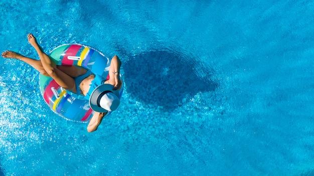 Piękna Dziewczyna W Kapeluszu W Basenie Z Lotu Ptaka Widok Z Góry, Młoda Kobieta Relaksuje Się I Pływa Na Dmuchanym Pierścieniu Pączka I Dobrze Się Bawi W Wodzie Na Rodzinne Wakacje, Tropikalny Ośrodek Wypoczynkowy Premium Zdjęcia