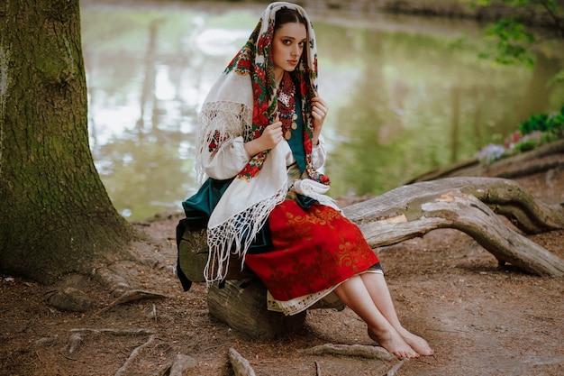 Piękna Dziewczyna W Tradycyjnym Etnicznym Stroju Siedzi Na ławce W Pobliżu Jeziora Darmowe Zdjęcia