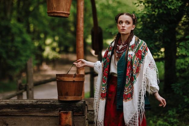 Piękna dziewczyna w tradycyjnym stroju etnicznym pozuje przy studni Darmowe Zdjęcia