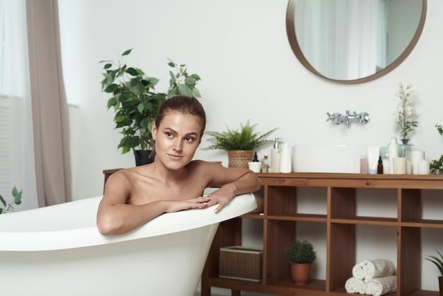 Piękna Dziewczyna Z Bielactwem Nabytym Leży W Wannie, Uśmiechając Się Do Kamery. ścieśniać. Zadowolona Piękna Młoda Kobieta Relaksująca Się Podczas Kąpieli. Premium Zdjęcia