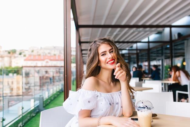 Piękna Dziewczyna Z Długimi Włosami Siedzi Przy Stole Na Tarasie W Kawiarni. Nosi Białą Sukienkę Z Odkrytymi Ramionami I Czerwoną Szminką. Ona Uśmiecha Się Do Kamery. Darmowe Zdjęcia