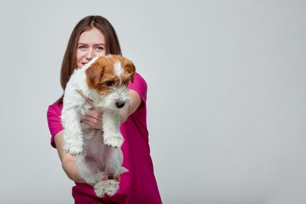 Piękna Dziewczyna Z Dźwigarki Russell Terierem Na Jej Rękach Na Szarym Tle, Kopii Przestrzeń Premium Zdjęcia
