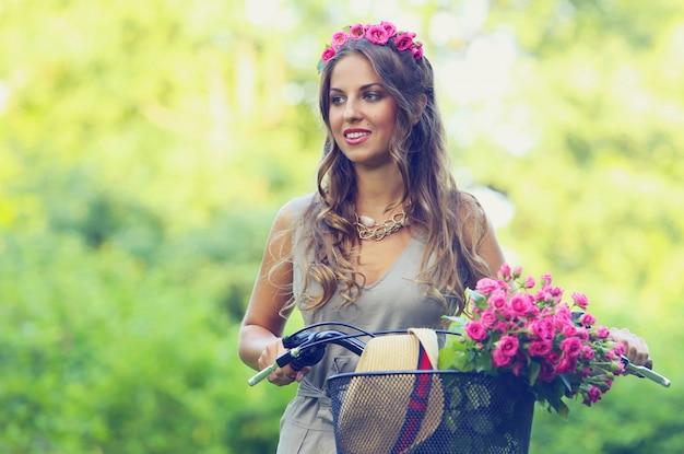 Piękna dziewczyna z kwiatami na rowerze Darmowe Zdjęcia