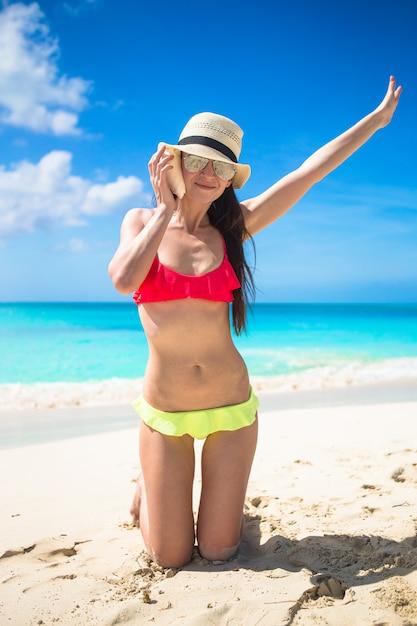 Piękna dziewczyna z seashell w rękach przy tropikalną plażą Premium Zdjęcia