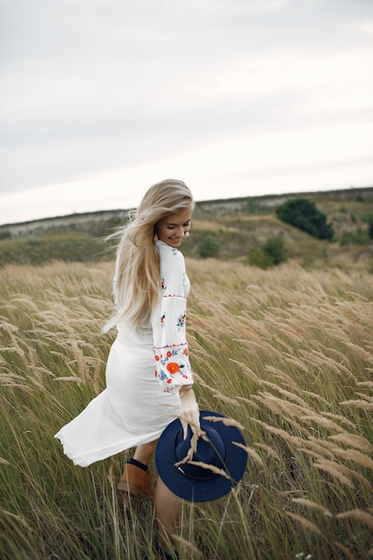 Piękna elegancka dziewczyna w polu pszenicy jesienią Darmowe Zdjęcia