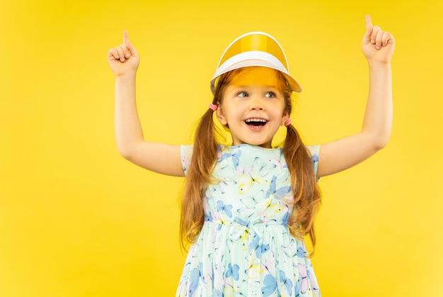 Piękna Emocjonalna Dziewczynka Na Białym Tle. Portret Szczęśliwego Dziecka Weard W Sukience I Pomarańczową Czapkę Skierowaną W Górę. Pojęcie Lata, Ludzkie Emocje, Dzieciństwo. Darmowe Zdjęcia